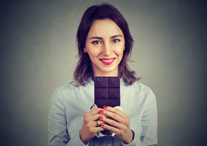 Portret młoda piękna dziewczyna trzyma ciemnego czekoladowego baru fotografia stock