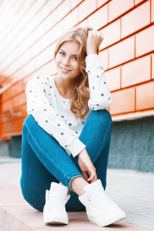 Portret młoda piękna dziewczyna w białym pulowerze, cajgi i obrazy royalty free
