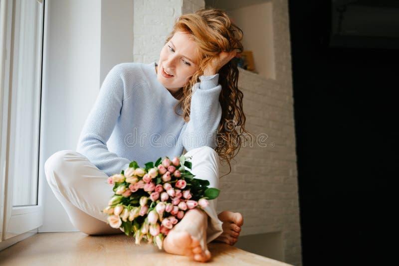 Portret młoda piękna dziewczyna z bukietem róże zbliża okno obrazy stock