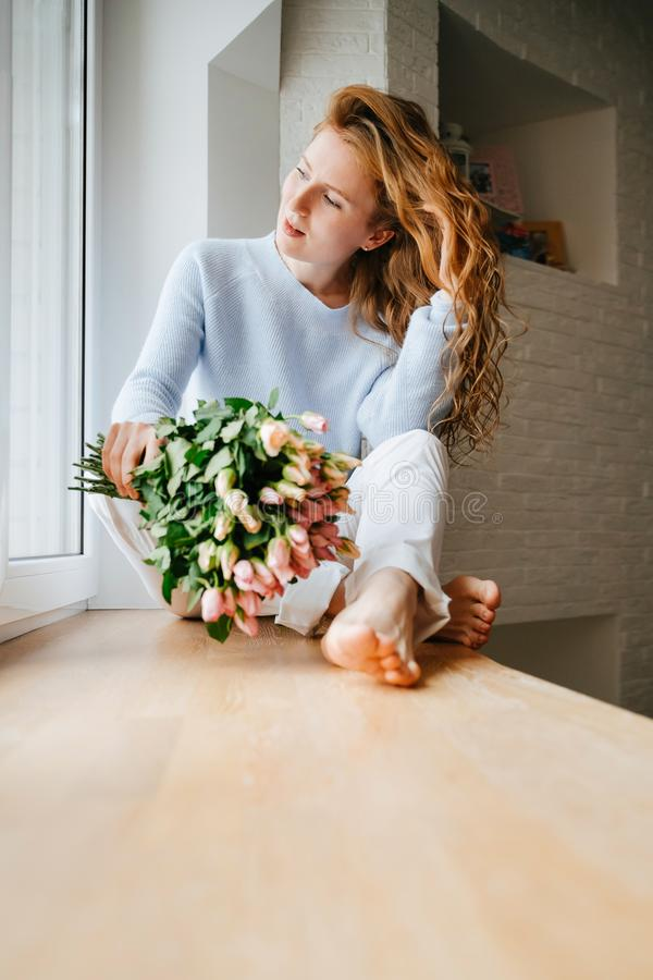 Portret młoda piękna dziewczyna z bukietem róże zbliża okno zdjęcie royalty free