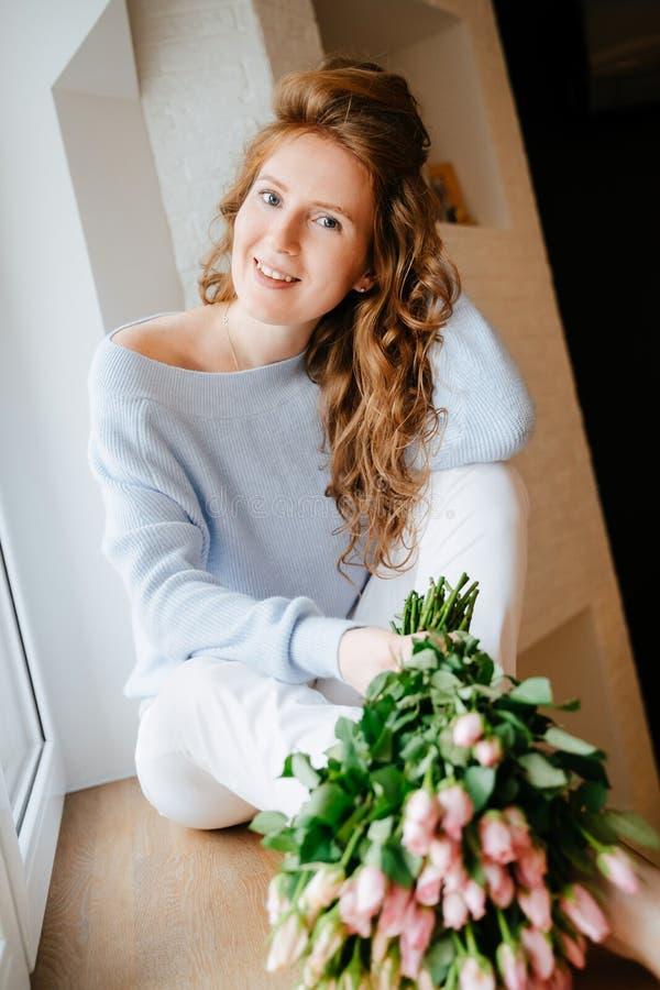 Portret młoda piękna dziewczyna z bukietem róże zbliża okno zdjęcie stock