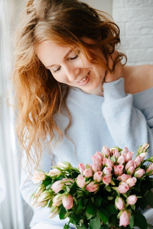 Portret młoda piękna dziewczyna z bukietem róże zbliża okno fotografia stock