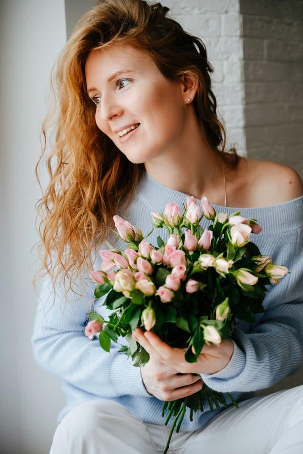 Portret młoda piękna dziewczyna z bukietem róże zbliża okno obraz royalty free