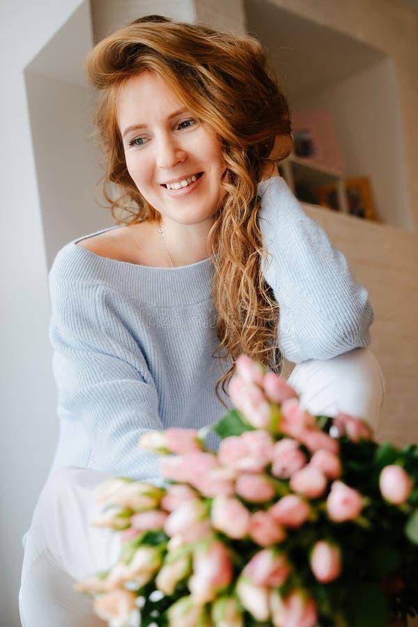 Portret młoda piękna dziewczyna z bukietem róże zbliża okno obraz stock