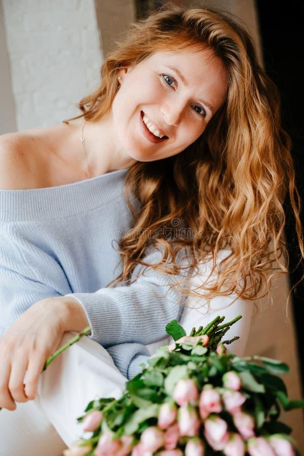 Portret młoda piękna dziewczyna z bukietem róże zbliża okno zdjęcia stock