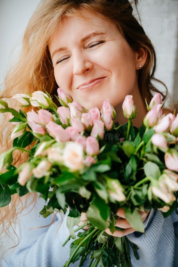 Portret młoda piękna dziewczyna z bukietem róże zbliża okno obrazy royalty free