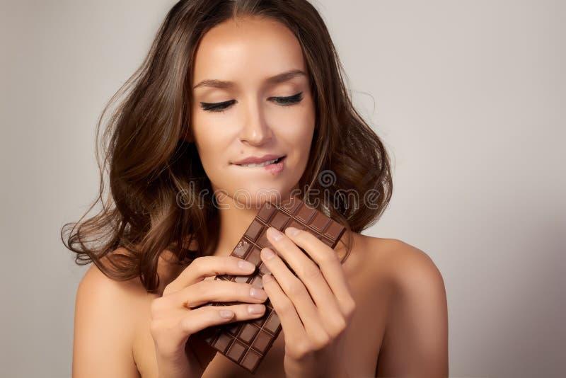 Portret młoda piękna dziewczyna z ciemnym kędzierzawym włosy, ogołaca ramiona i szyję trzyma czekoladowego baru cieszyć się a i s obrazy royalty free