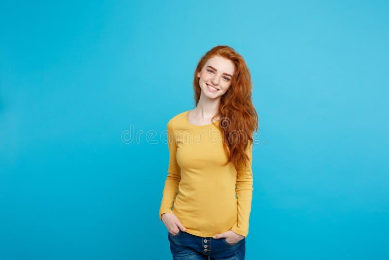 Portret młoda piękna imbirowa kobieta cheerfuly ono uśmiecha się z piegami patrzejący kamerę Odizolowywający na pastelowym błękic obrazy stock