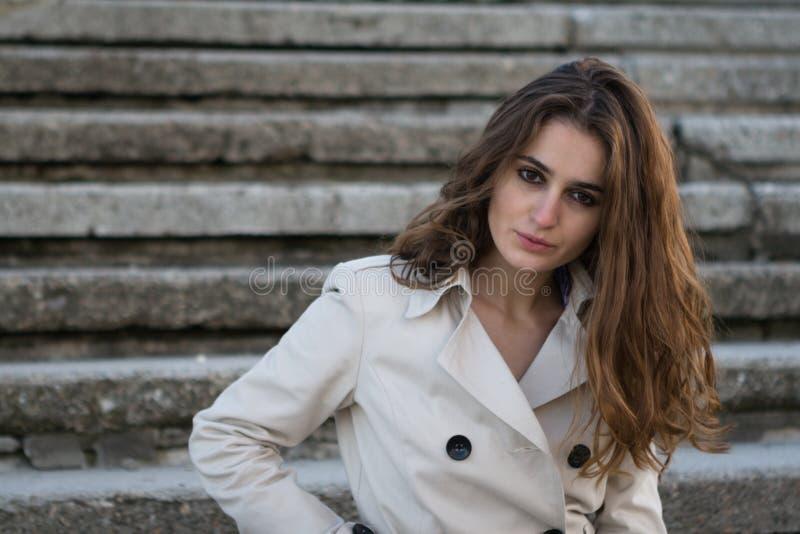 Portret młoda piękna kobieta jest ubranym kurtkę nad schodka tłem _ zdjęcia royalty free