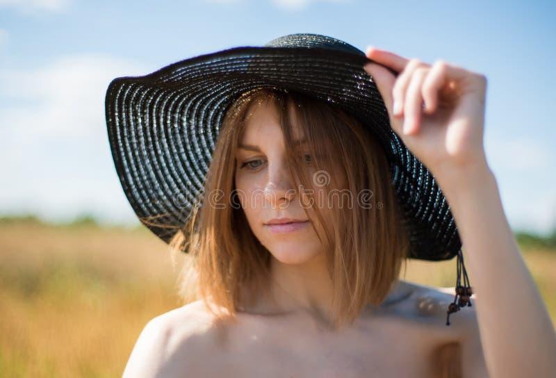 Portret młoda piękna kobieta w kapeluszu na polu zdjęcie stock