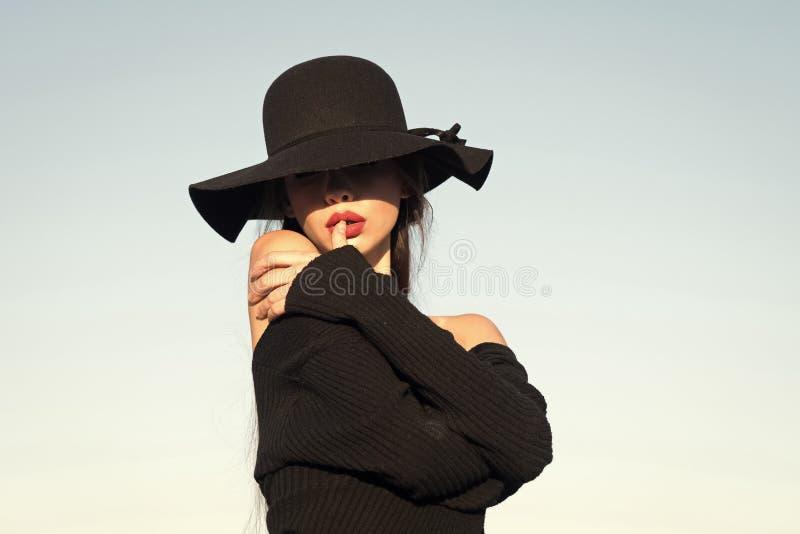 Portret młoda piękna modna kobieta jest ubranym eleganckich akcesoria Chowani oczy z kapeluszem Żeńska moda zdjęcia royalty free