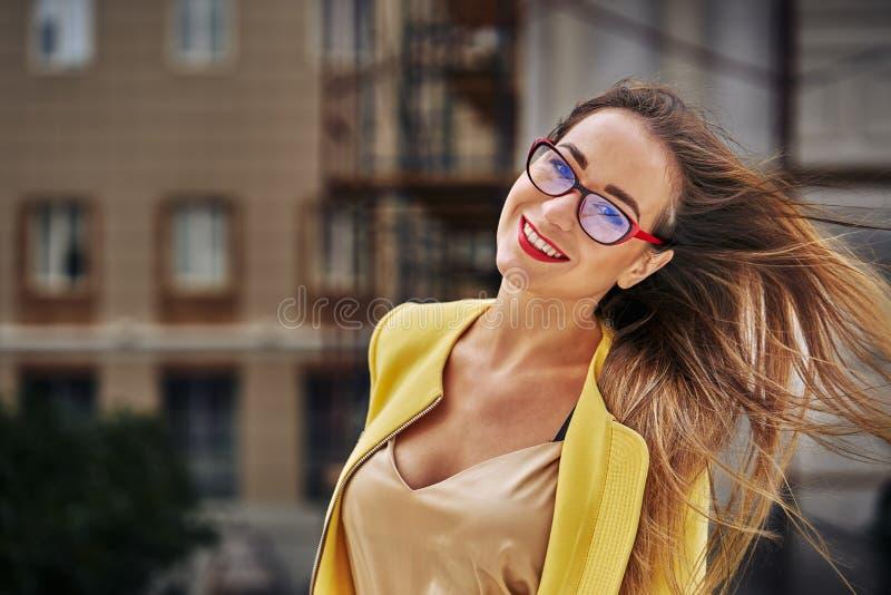 Portret młoda piękna roześmiana kobieta z długie włosy jest ubranym szkłami i żółtą kurtką zdjęcie royalty free
