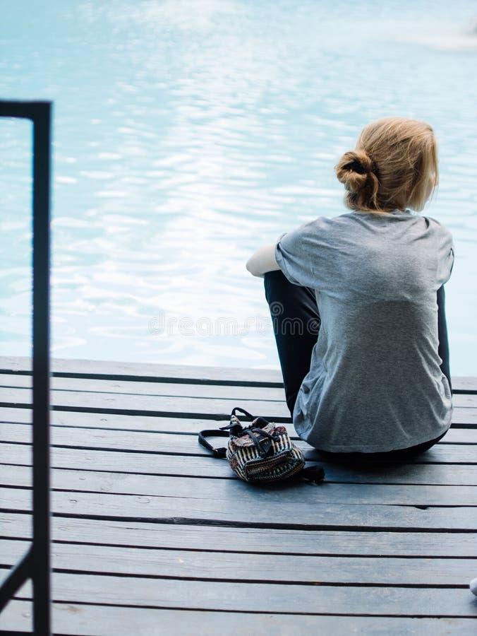 Portret Młoda Piękna Uśmiechnięta blondynki dziewczyna Używa Smartphone podczas gdy Siedzący na moscie zdjęcia royalty free
