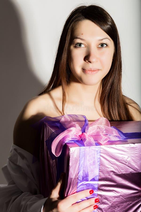 Portret młoda piękna uśmiechnięta dziewczyna w mężczyzna ` s białej koszula, trzymający prezent i cieszy się zdjęcia royalty free