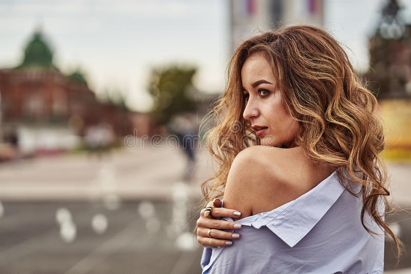 Portret młoda piękna zadumana kobieta z brązu długim kędzierzawym włosy i brązem przygląda się patrzeć w odległość zdjęcie stock
