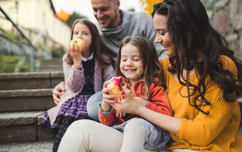 Portret młoda rodzina z dwa małymi dziećmi w miasteczku w jesieni zdjęcie stock