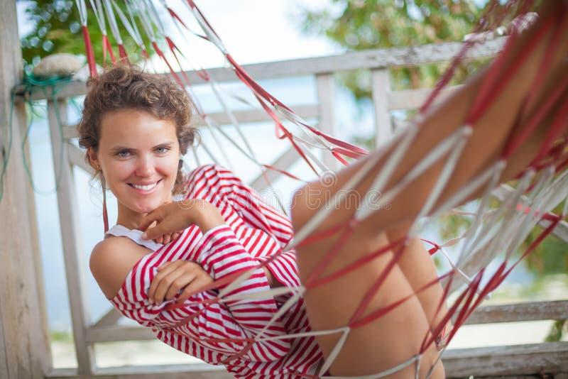 Portret młoda seksowna dziewczyna relaksuje na plażowym bungalowie w hamaku Uśmiechniętego kobieta wydatków chłodu czasu plenerow obrazy royalty free