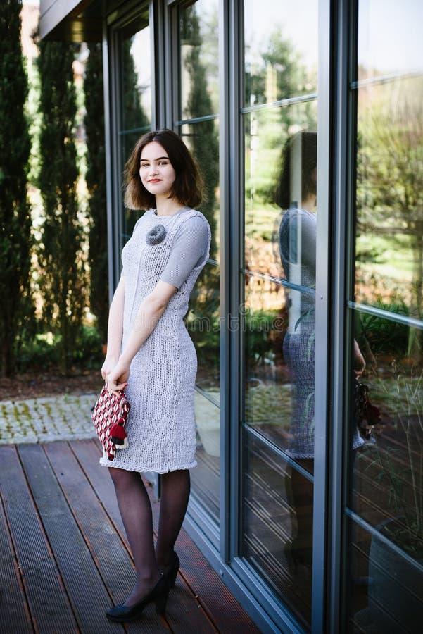 Portret młoda szczęśliwa kobieta w popielatej trykotowej sukni obraz stock