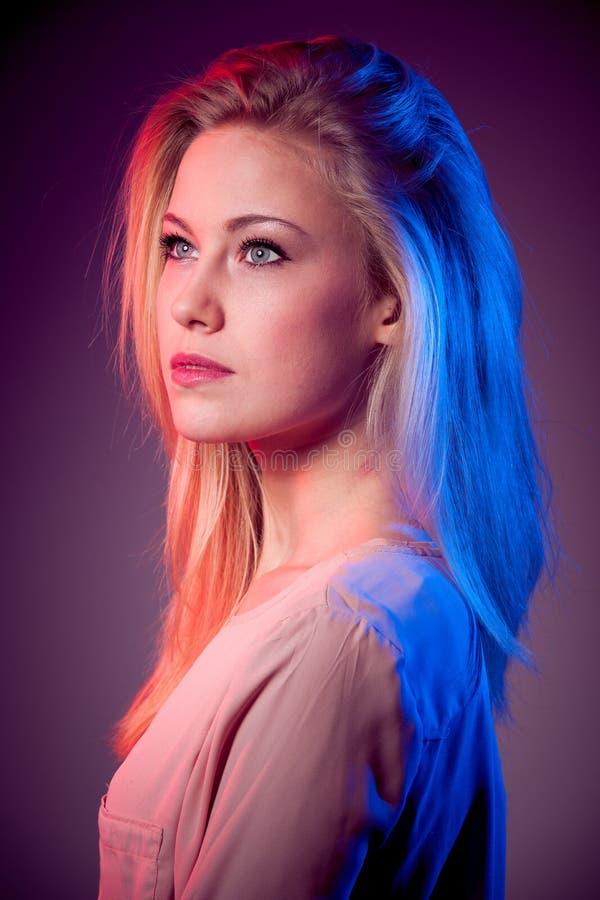 Portret młoda szczęśliwa uśmiechnięta kobieta z błękitem i czerwony połysk światło na włosy obrazy stock