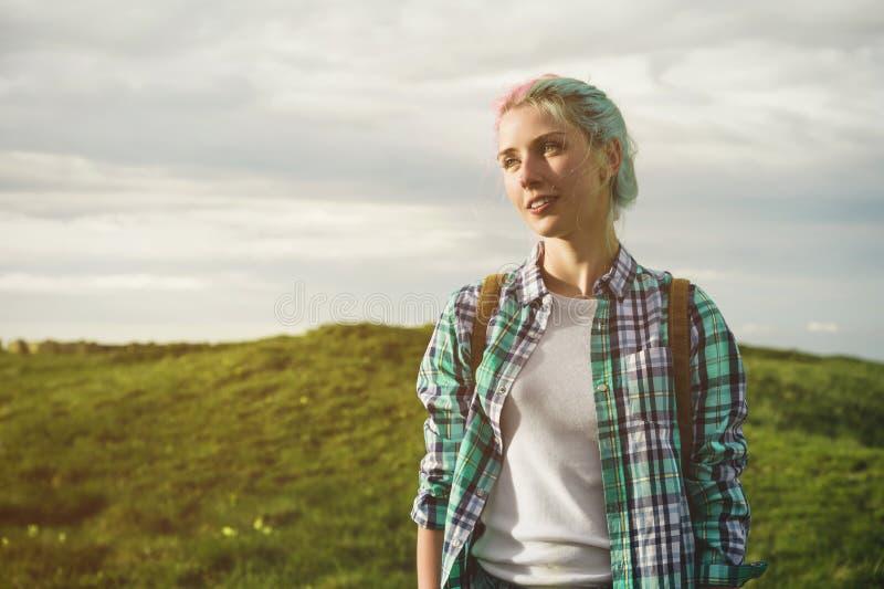 Portret młoda uśmiechnięta atrakcyjna kobieta w szkockiej kraty koszula odziewa z małym plecakiem przy słonecznym dniem na chmurn obraz royalty free