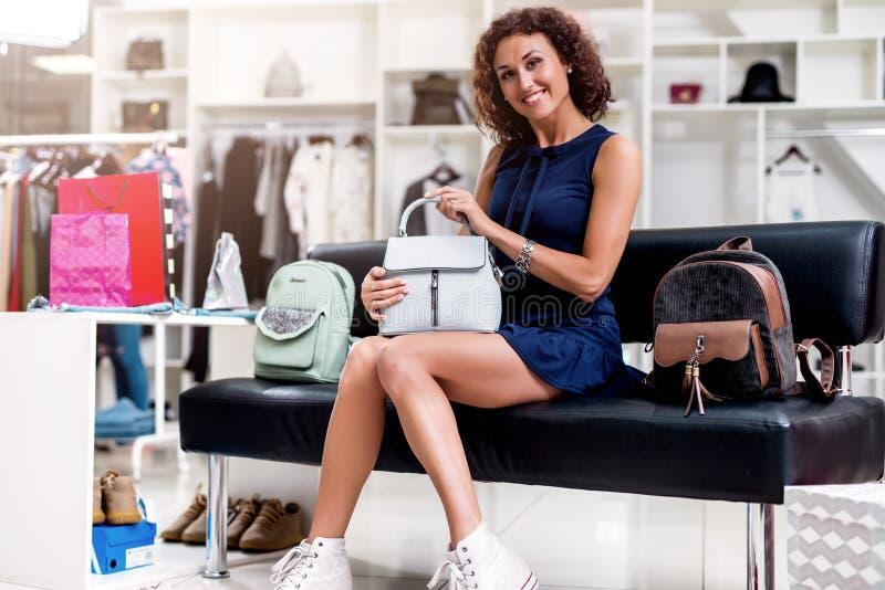 Portret młoda uśmiechnięta brunetka podnosi nową torebkę podczas gdy siedzący na ławce patrzeje kamerę w sklepie odzieżowym obraz royalty free