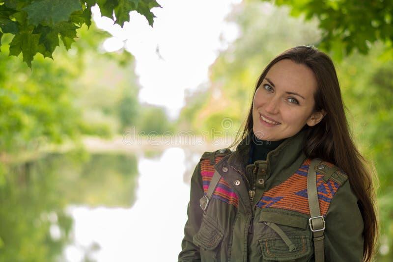 Portret młoda uśmiechnięta brunetka w zielonym parku z jeziorem kosmos kopii obraz royalty free
