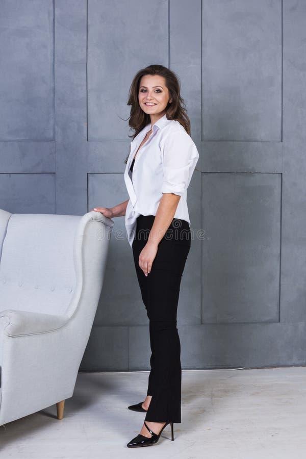Portret młoda uśmiechnięta kobieta na szarym ściennym tle Piękna dziewczyna w białej koszula i czarni bielizna stojaki blisko con fotografia royalty free