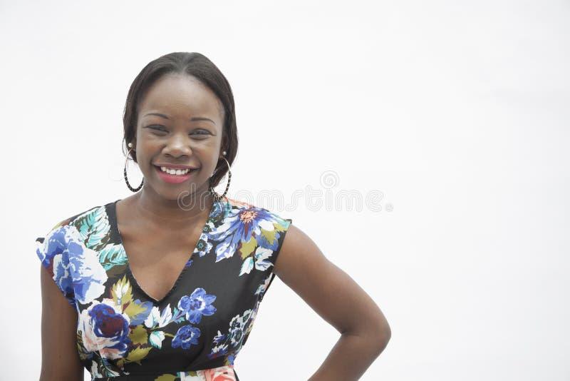 Portret młoda uśmiechnięta kobieta z ręką na biodrze w tradycyjnej odzieży od Afryka, studio strzał obrazy stock