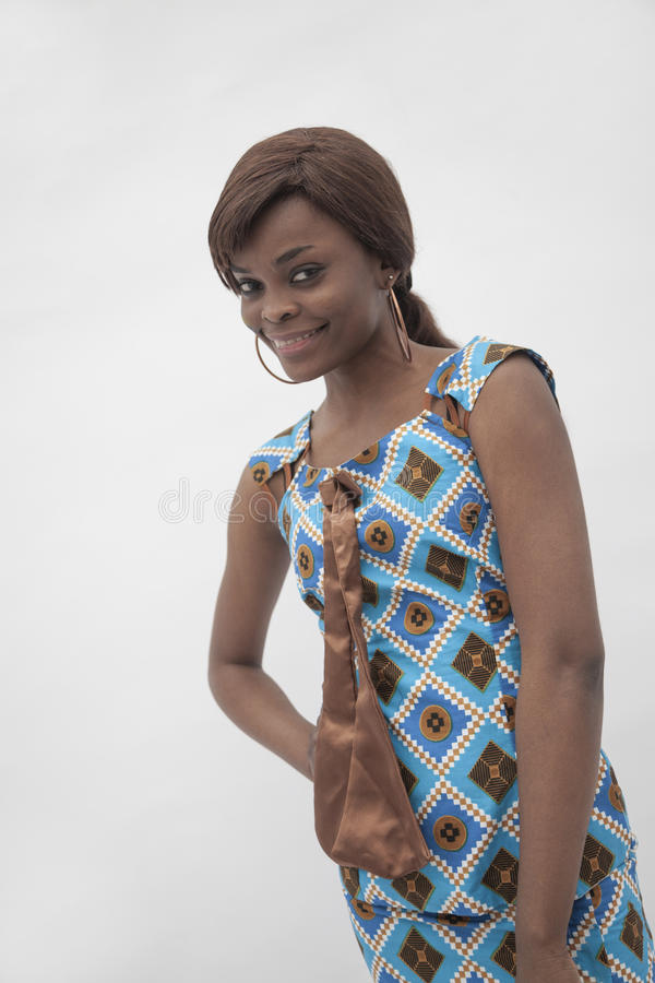 Portret młoda uśmiechnięta kobieta z ręką na jej biodrze w tradycyjnej sukni od Afryka, studio strzał obraz royalty free