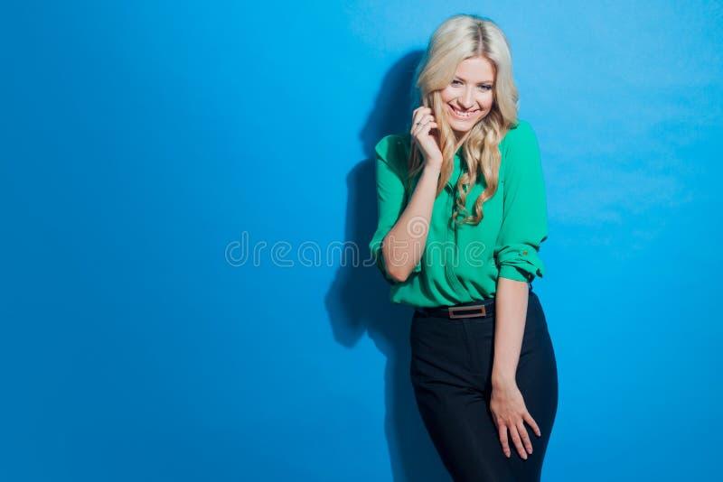 Portret młoda ufna blondynka, przypadkowy styl, błękitny tło fotografia royalty free