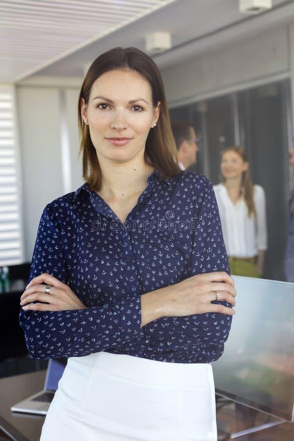 Portret młode bizneswoman pozyci ręki krzyżował z kolegami w tle przy biurem zdjęcia stock