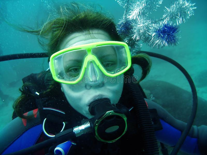 Portret młode kobiety z akwalungu nurkowym wyposażeniem: maska, regulator i akcesoria na jej dziedzic, Jest podwodna, ona patrzej zdjęcie stock