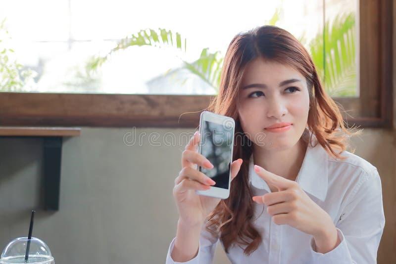 Portret młodego atrakcyjnego Azjatyckiego biznesowej kobiety mienia mobilny mądrze telefon i patrzeć kamerę w sklep z kawą z kopi obrazy stock