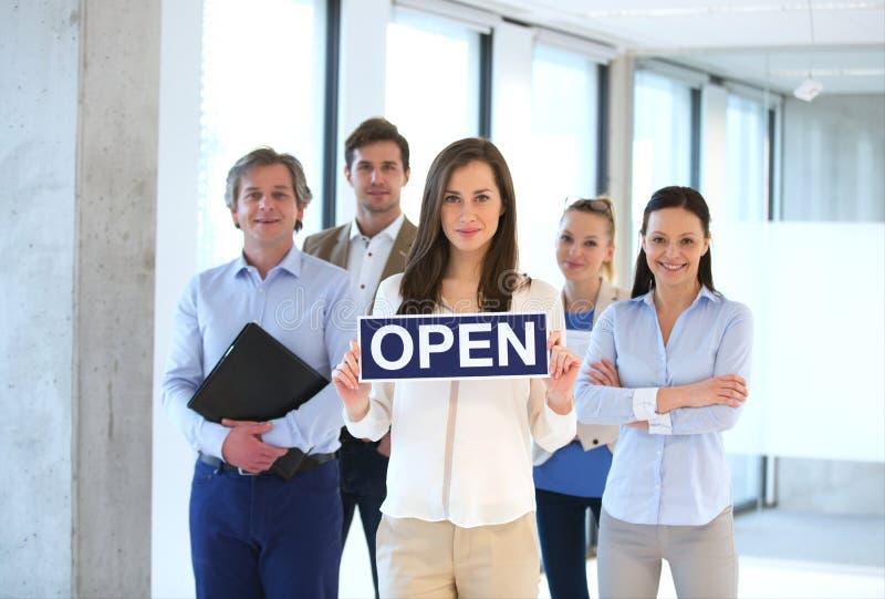 Portret młodego bizneswomanu mienia otwarty znak z drużyną behind przy biurem fotografia stock