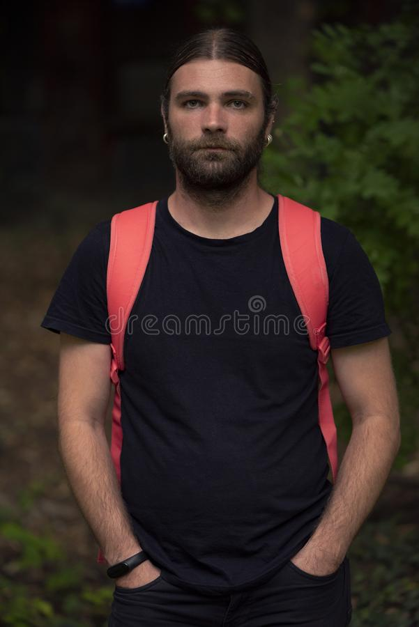 Portret młodego, brodatego mężczyzny w naturalnym świetle, z rękami w kieszeniach, patrzącego na kamerę z czujnością fotografia royalty free