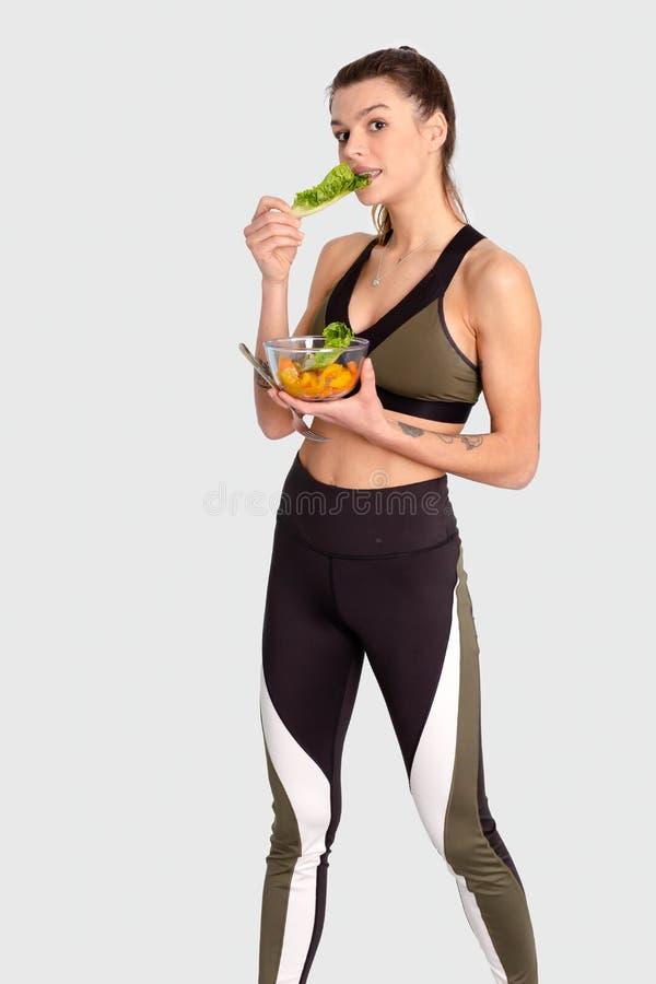 Portret młodego caucasian kobiety mienia i łasowania świeżego warzywa sałatka na białym tle obrazy stock