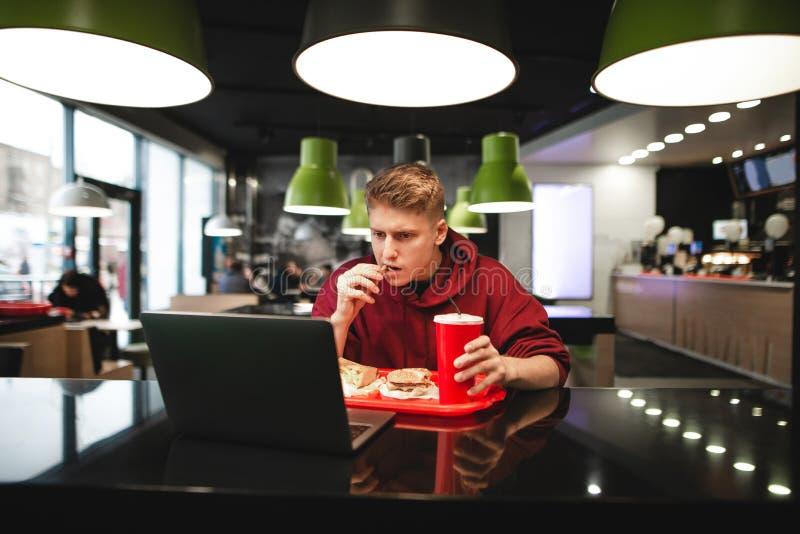 Portret młodego człowieka łasowania fast food przy restauracją i używać laptop obraz stock