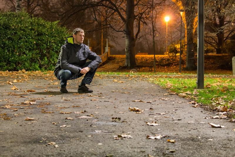 Portret młodego człowieka obsiadanie na ulicie w miasto parku przy nocą fotografia royalty free