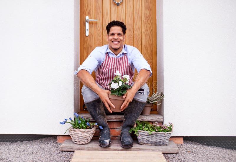 Portret młodego człowieka obsiadanie przed drzwi w domu, flancowanie kwitnie obraz royalty free