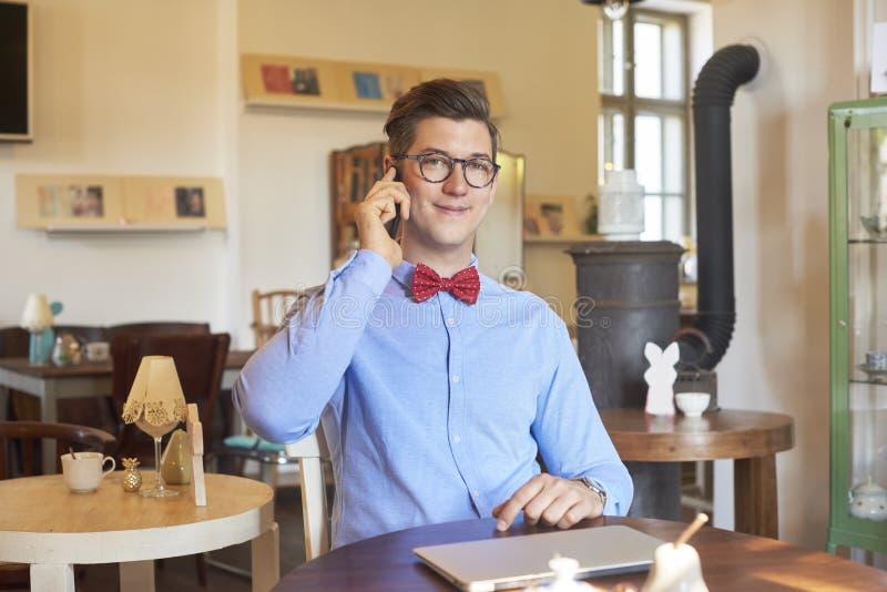 Portret młodego człowieka obsiadanie przy kawiarnią i opowiadać z somebody na jego telefonie komórkowym zdjęcia royalty free