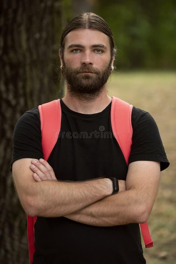 Portret młodego mężczyzny w naturalnym świetle, wyglądający defensywnie, trzymając ramiona przekreślone i nosząc czarną  obraz stock