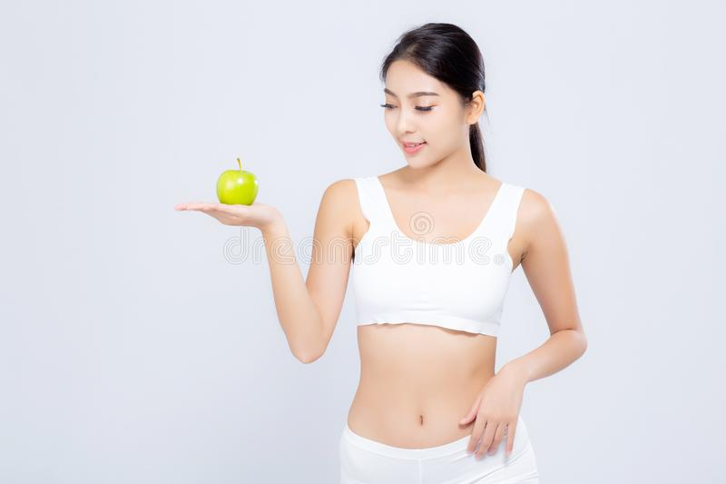 Portret młodej azjatykciej kobiety mienia zieleni uśmiechnięty jabłko i piękna ciało dieta z napadem odizolowywającym obrazy stock