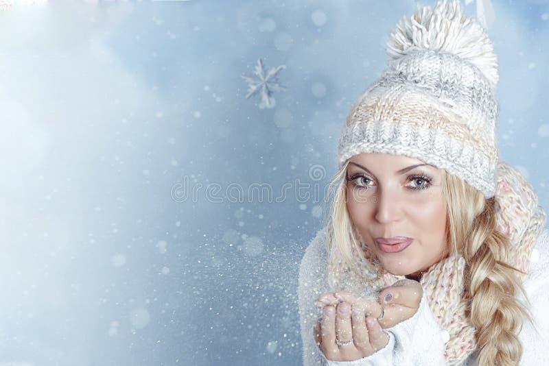 Portret młodej blondynki o jasnych oczach w kapeluszu zimowym i szalik wysadzający migoczący śnieg z jej ręki Boże Narodzenie-Now zdjęcie stock