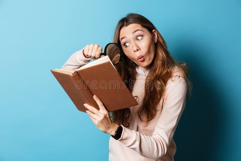 Portret młodej dziewczyny czytelnicza książka z powiększać - szkło zdjęcia stock