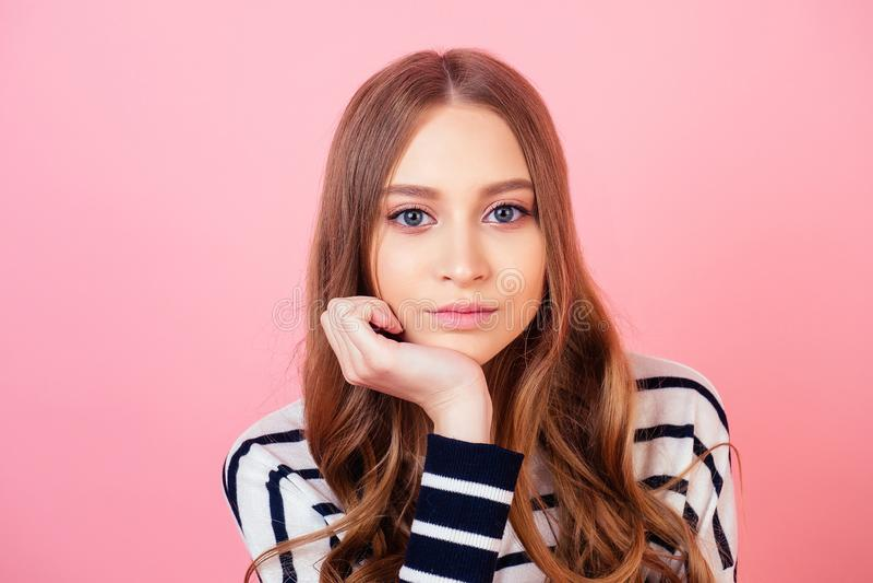 Portret młodej i pięknej uczennicy znudzonej i myślącej w studiu na różowym tle obrazy royalty free