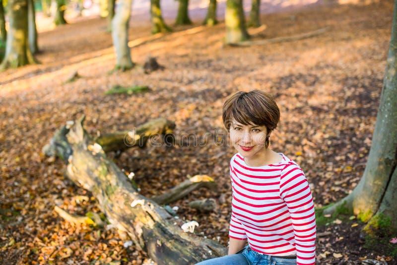Portret młodej kobiety relaksować na spadać drzewie w jesiennej lasowej patrzeje kamerze i obsiadanie, uśmiechnięta dziewczyna Je obrazy royalty free