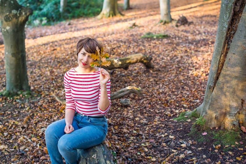 Portret młodej kobiety relaksować na spadać drzewie w jesiennej lasowej patrzeje kamerze i obsiadanie, uśmiechnięta dziewczyna Je obraz royalty free