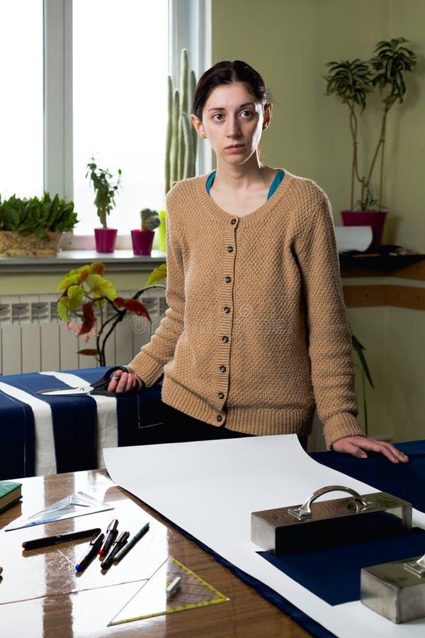 Portret młodej kobiety szwaczka w domowym studiu Patrzeje appraisingly przy klientem Trzymać parę nożyce (zestaw) Handmade poj?ci obraz stock