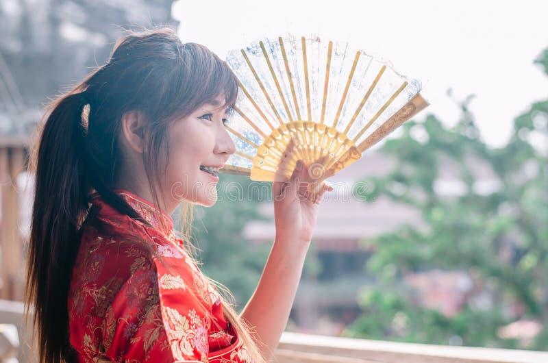 Portret młodej kobiety uśmiechu odzieży piękny cheongsam głęboki - czerwieni smokingowy mienie fan patrzeje outside Gody i święto zdjęcie royalty free