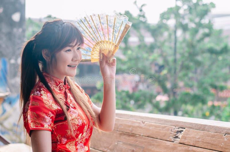 Portret młodej kobiety uśmiechu odzieży piękny cheongsam głęboki - czerwieni smokingowy mienie fan patrzeje outside Gody i święto obrazy stock